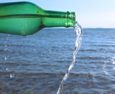 Water pouring from glass bottle into water — Stock Photo