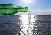 Water gieten van glazen fles in water — Stockfoto