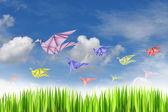 Paper birds on blue sky background — Stock Photo