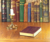 Old book and candle — Stock Photo