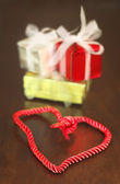 Gifts and heart shaped braid — Stock Photo