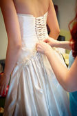 Bridesmaid tightening bride corset — Stock Photo