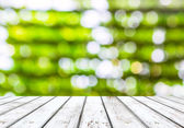 Empty wooden plank and green bokeh background — Foto Stock