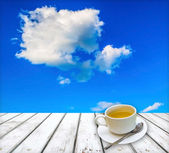 Tea cup on wooden table with sky background — ストック写真