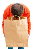 Man looking inside paper bag. — Stock Photo