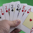 Hand holding a royal flush hearts on green — Stock Photo #34250617