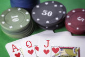 Poker chips and cards on green — Stock Photo