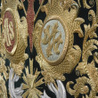 Embroidery thread of gold on green velvet with the acronym for Christ and Mary — Stock Photo