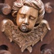 Cherub with suck on wood carving — Stock Photo