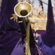 Penitent purple tunic holds a trumpet during Holy week procession — Stock Photo