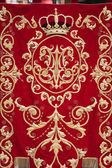 Embroidery thread of gold on red velvet — Stock Photo