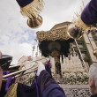 Penitents touch large trumpets to Virgen de los Dolores in a procession of holy week — Stock Photo