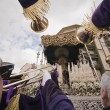 Stock Photo: Penitents touch large trumpets to Virgen de los Dolores in procession of holy week
