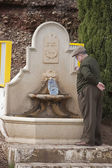 Old man filling a bottle of drinking water in a fountain — Stock Photo