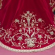 Stock Photo: Embroidering with gold thread work on red velvet