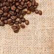Coffee beans on burlap fabric — Stock Photo