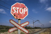 Warning sign worn of level crossing without barriers, blue sky with clouds — Stock Photo
