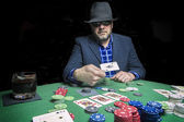 Man with hat and glasses of the sun bets in a poker game — Stockfoto
