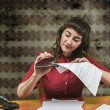 Stock Photo: Young womwith red dress stapling papers in office, 1960's