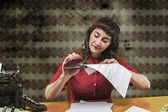 Young woman with red dress stapling papers in office, 1960's — Stock Photo