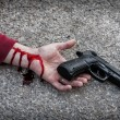 Stock Photo: Mwith gun in hand bloodstained lies dead in asphalt murde