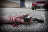 Man with gun in hand bloodstained lies dead in the asphalt murde — Stock Photo
