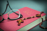 Glasses adjusted on the holy bible and beads — Stock Photo
