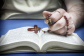 Christian believer praying to God with rosary in hand — Stock Photo