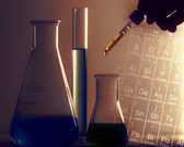 Laboratory glassware and arm with pipette — Stock Photo