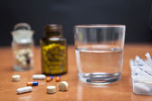 Old bottle of pills along with a few pills above a wooden table — Foto de Stock