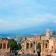 Ancient greek amphitheatre in Taormina city and mountain Etna in the back, Sicily island, Italy — Stock Photo #40972403
