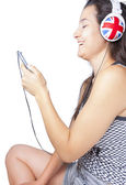 Young girl smiling with phone and headphones — Foto Stock