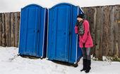 Woman waiting outside toilette — Stock Photo