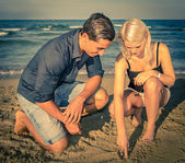 Hansome man and pretty woman spending time on the beach — Stock Photo