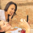 Two beautiful women looking enthusiastic at mobile phone — Stockfoto