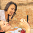 图库照片: Two beautiful women looking enthusiastic at mobile phone