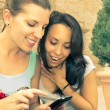 Two beautiful women looking enthusiastic at mobile phone — Zdjęcie stockowe