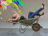 Happy girl in a barrow with color splash — Stock Photo