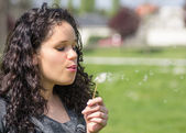 Woman blow flower away — Stock Photo