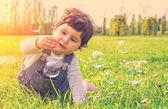 Baby playing with soap bubbles — Stock Photo
