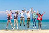 Friends jumping on the beach — Stock Photo