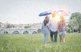 Friends walking in the rain — Stock Photo