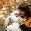Newborn on the mother's hands in the park in autumn — Stock Photo