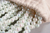 White pearls poured out of the bag — Stock Photo