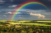 Village landscape with rainbow on  dramatic cloudy sky, natural  — Stock Photo
