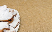 Cookies sprinkled powder on brown sack texture — Stock fotografie