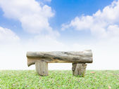 Log bench on a green grass with  blue sky  — Stock Photo