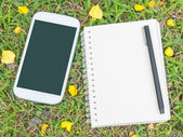 Cream notebook with pen and mobile phone on green grass — Stock Photo