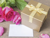 Gold gift box with card and rose  — Stock Photo