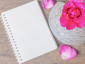 Notepad and pink rose in vase — Stock Photo